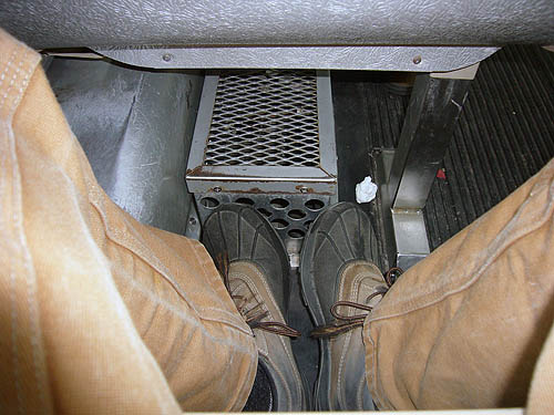My feet, in L.L. Bean duckboots, jammed under a bus seat and behind a corrugated steel box