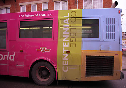 Rear half of bus advertises Centennial College in solid patches of magenta, chartreuse, and blue and orange