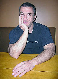 Stephen Cox in black T-shirt, chin resting on one hand