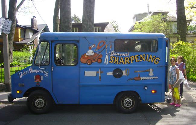 Women mingle behind hand-painted John's General Sharpening van
