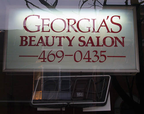 Sign reads GEORGIA'S BEAUTY SALON and a phone number in Palatino, with a neon OPEN sign turned off underneath
