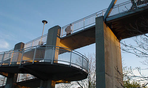 Concrete footbridge seen at twilight has a winding downward ramp on one end