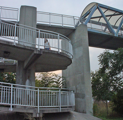 Woman walks along concrete walkway that curves up two levels to a covered bridge