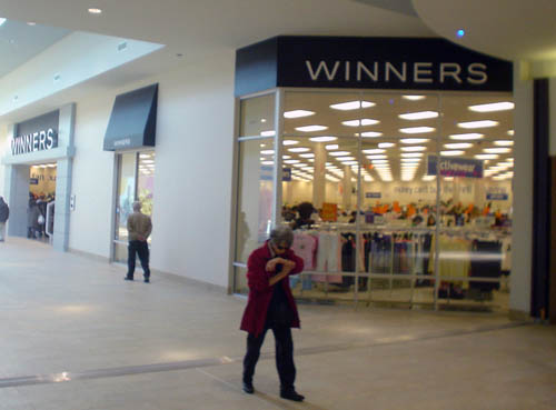Store in corner location of mall has signs reading WINNERS as woman passing by checks her watch