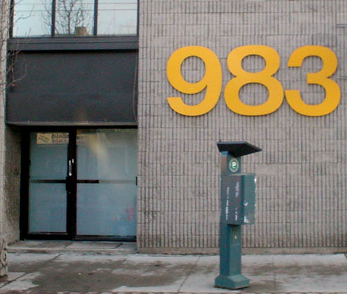 Grey-brick building behind parking-ticket dispenser is labeled 983 in giant yellow Helvetica