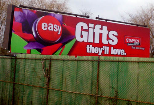 Red billboard towers above green fence and reads 'Gifts they'll love.' in white Helvetica Condensed