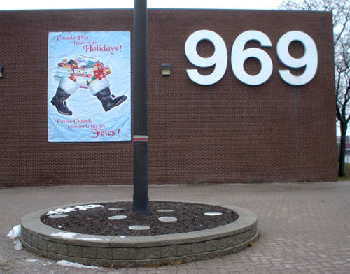 Brick building is labeled 969 in giant Helvetica, with a sign reading Canada Post Delivers the Holidays! showing Santa's trousers full of gifts