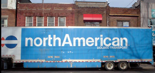 Blue moving van is labeled northAmerican DOLBEC TRANSPORT in Helvetica (with lower-case t with no stem on the left)