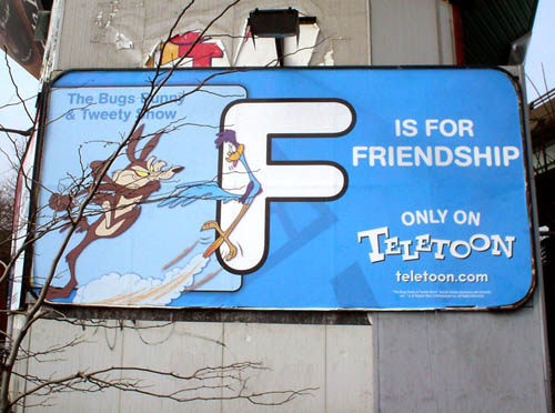 Billboard, mounted on decaying concrete post behind denuded tree, shows Wile E. Coyote chasing the Roadrunner and F IS FOR FRIENDSHIP in Helvetica Rounded