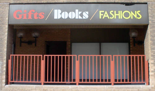 Orange-railed balcony is topped by a sign reading Gifts/Books/FASHIONS in a different font per word