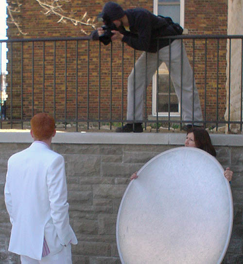 Woman holds large round light reflector at a red-haired man in a white suit, who faces away as another man aims a camera down at him from an upper-level fence