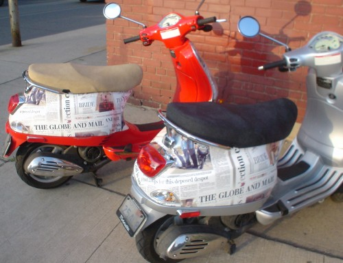 Silve and red scooters have rear ends covered in identical 'Globe and Mail' wallpaper