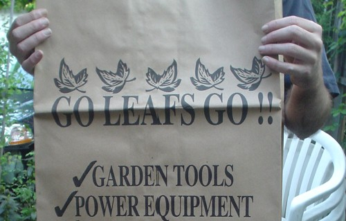 Hands hold brown paper bag labeled GO LEAFS GO !! ✔GARDEN TOOLS ✔POWER EQUIPMENT in squeezed Times type