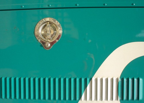 Teal-blue metal panel, with ventilation grille at bottom, also has a bright-gold-coloured round brass latch