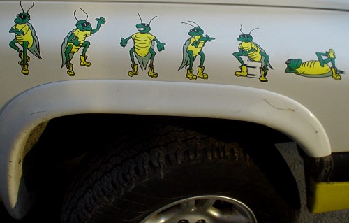 Truck fender has illustrations of six green-and-yellow grasshoppers in workboots and shades striking different poses, with the last two seated and stretched out on its back