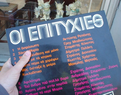 Hand holds Greek LP record entitled OI E∏ITYXIES