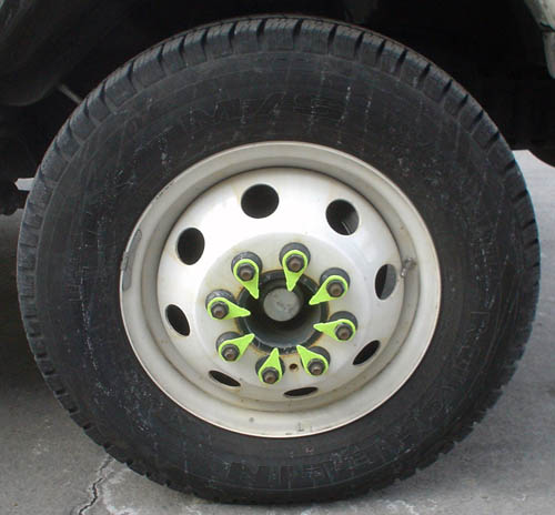Truck tire surrounds whit ewheel whose inside bolts all have neon-gren triangular tabs pointing inward