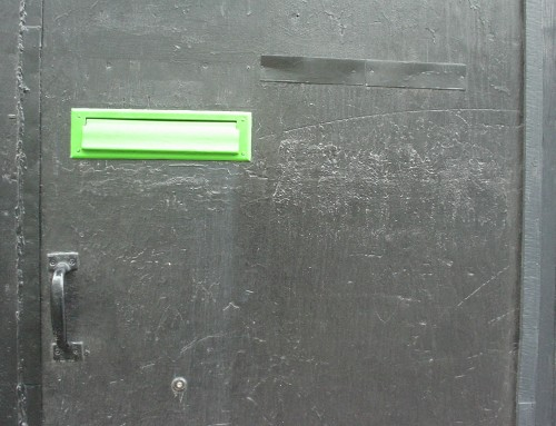 Scratched aluminum door sports a piece of silver tape and a neon-green mail slot
