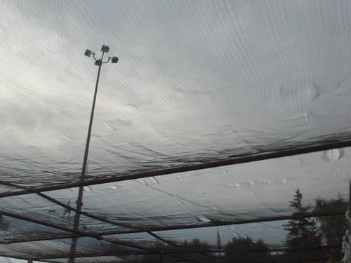 Grey clouds show through metal-framed tarpaulin roof