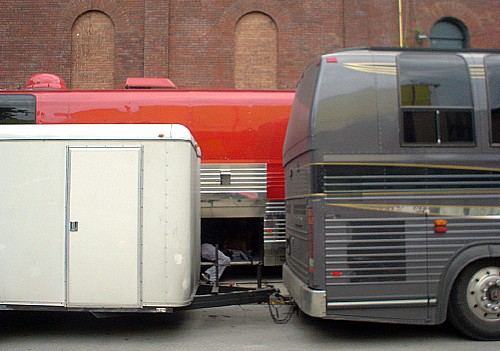 Visible between a grey tour bus and its trailer, a man crouches in luggage hold of red tour bus