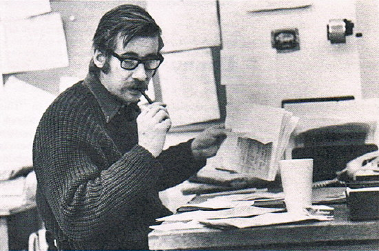 Peter Gzowski, in heavy cabled sweater, ruffles papers and looks at desk while smoking a pipe