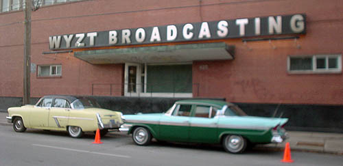 Brick building has sign over entrance reading WZYT BROADCASTING in Arial Black, with two vintage cars parked on the street next to orange pylons