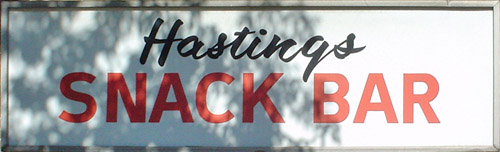 Branches cast shadows on a sign reading 'Hastings Snack Bar,' with 'Hastings' in hand-drawn script