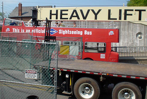 Fence with DANGER sign, flat bed of truck, London-style red sightseeing bus, arm reading HEAVY LIFT, concrete wall, house