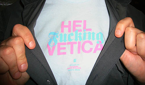 Hands hold open a shirt to reveal a blue T-shirt with pink-and-blue type reading HEL Fucking VETICA