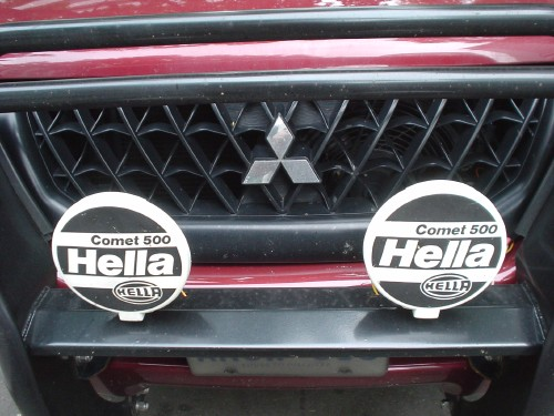 Covers on twin driving lamps attached to a Mitsubishi bumper read Comet 500 Hella in Helvetica