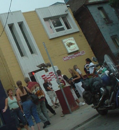 Men in T-shirts and vests and women in tank tops and tube tops mill about outside building labeled Hells Angels Toronto