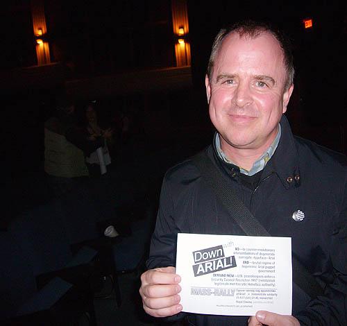 In a darkened theatre, Gary Hustwit grins and holds a Down with Arial! handbill