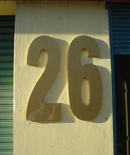 Raised Helvetica Condensed letters on building read '26' in the afternoon sun