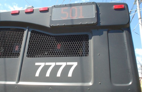 Rear of slate-grey Route 501 bus is labeled with '7777' in Helvetica