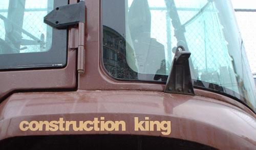 Fender of brown truck is emblazoned 'construction king' in Helvetica