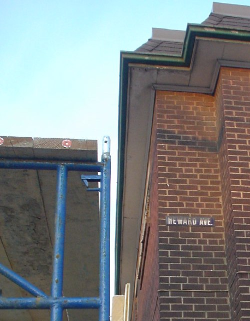 Blue scaffolding next to brick low-rise apartment block bearing 'Heward Ave.' sign
