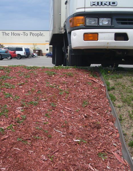 Hino truck perched on parking lot above steeply-raked patch of red gravel