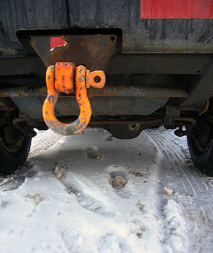 Trailer-hitch loop, its orange paint rubbed off in places, hangs from black bumper