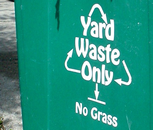 Green recycling bin is labeled 'Yard Waste Only No Grass' in the font known as Hobo