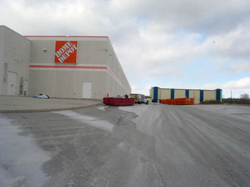 Barren greay-and-white parking ramp leads to barren grey-and-white two-storey concrete building with orange Home Depot sign and single orange stripe. Warehouse and dumpsters sit on the ramp