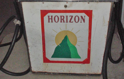 Dilapidated gas pump shows a logo of a sun rising behind a green mountain with the heading 'Horizon'