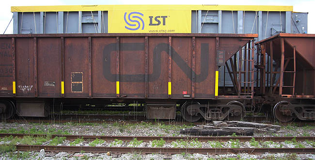 Rusted CN freightcar sits in front of new silver-and-yellow boxcar labelled IST