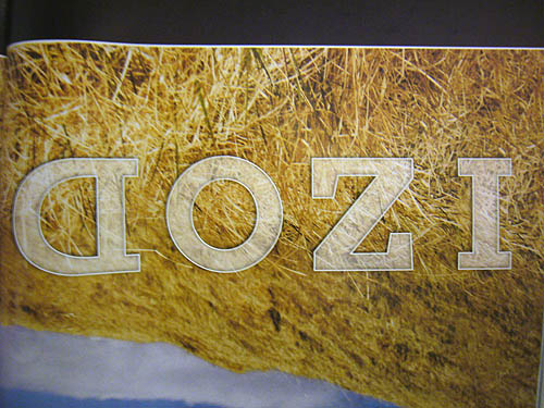 Upside down, translucent letters atop a photo of hay read IZOD