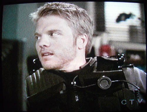 Photo of TV screen: David Paetkau, in combat vest, turns his head to the side