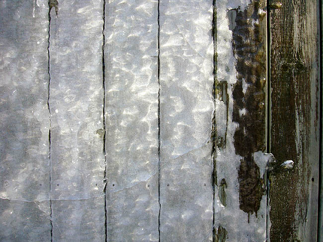 Ragged sheet of ice covers most of a set of wooden planks