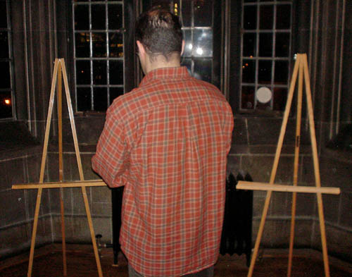 Balding man in red plaid shirt faces away and stands in a bay window between empty wooden easels