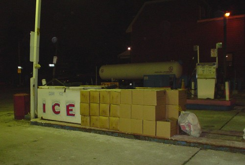 Dark, ocherous photo shows gas-station ice machine alongside piles of boxes of the same height