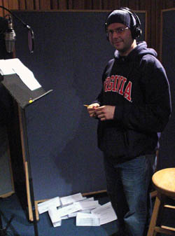 Jeremy Harris, in hoodie, toque, and headphones, stands amid crumpled pages in a recording booth