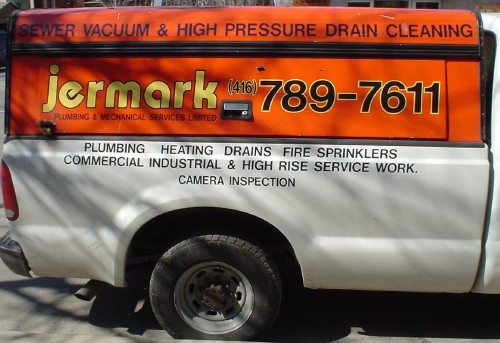 Orange cap on white pickup truck has the word 'jermark' in hand-drawn Bauhaus font and a phone number in black Helvetica outlined in yellow