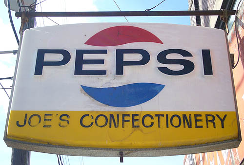 Sign with the word PEPSI between red and blue quarter-circle waves above and below, and JOE'S CONFECTIONERY on a yellow background